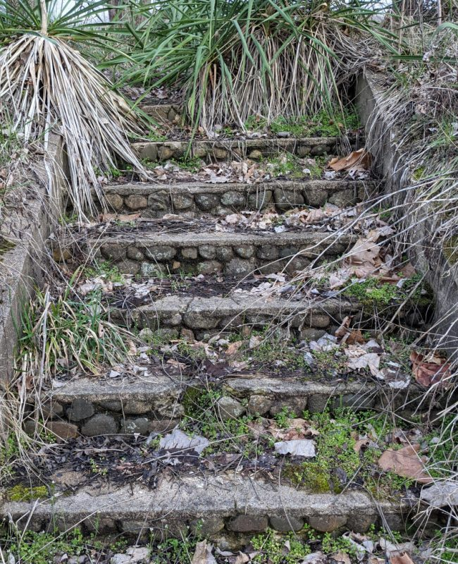 Short set of stairs made of concrete and smooth river rocks
